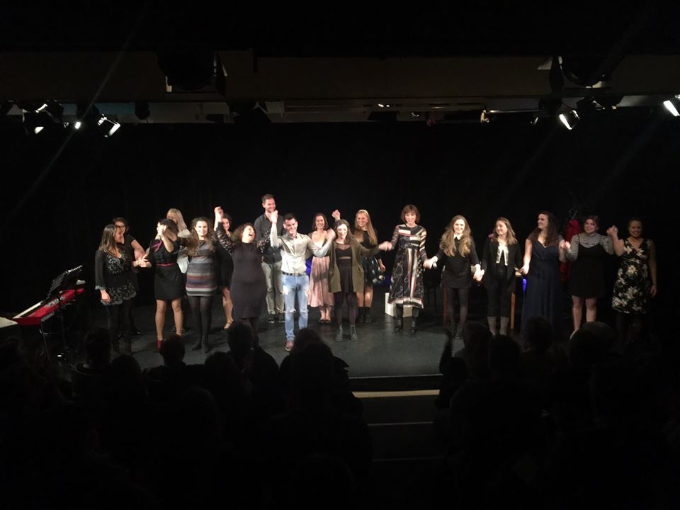 Eine Gruppe von Gesangsschülern steht auf einer schwarzen Bühne und verbeugt sich.